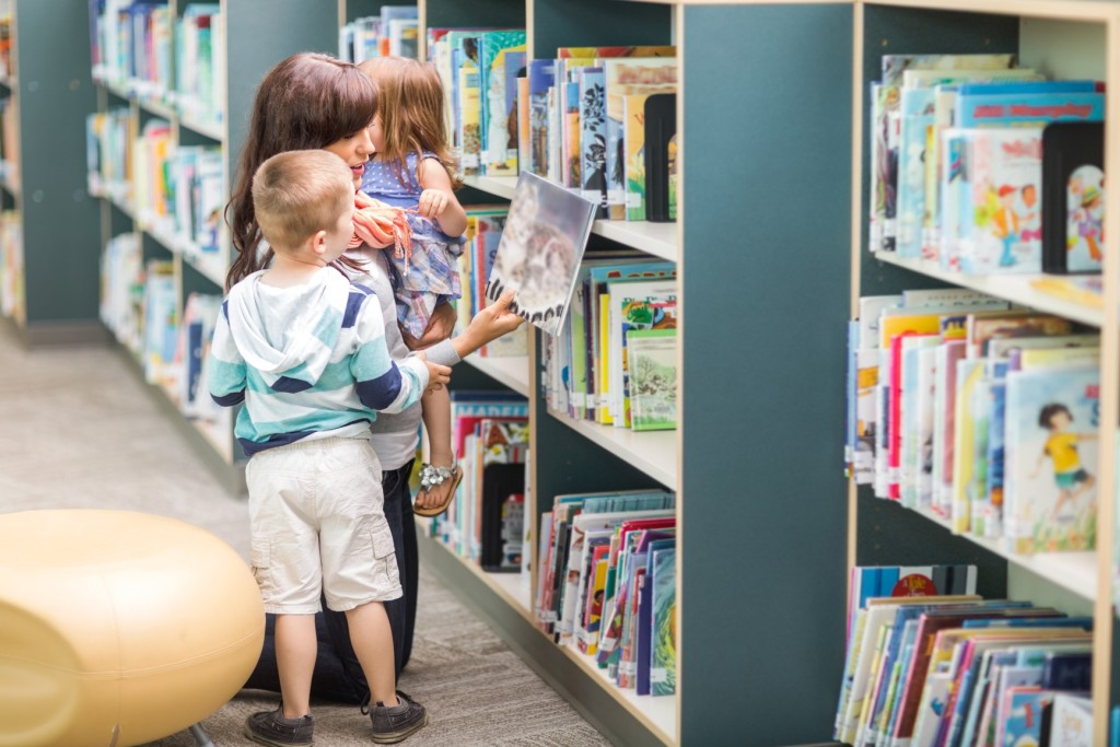 Young teacher with children selecting book from bookshelf in library